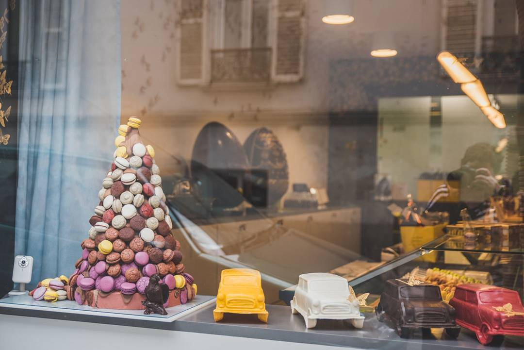 Peeking through a Paris shop window at a literal tower of macarons, giant chocolate eggs, and edible cars! Is that a little camera in the corner so they can see how many people press their faces to the glass and drool?
